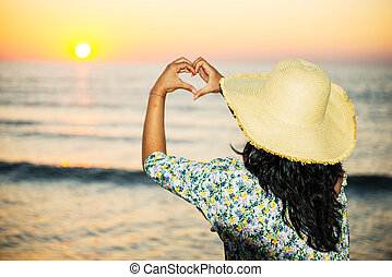 Woman shape heart with hands to sunrise at sea