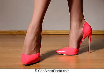 woman shapely legs wearing in fashionable pink lacquered...