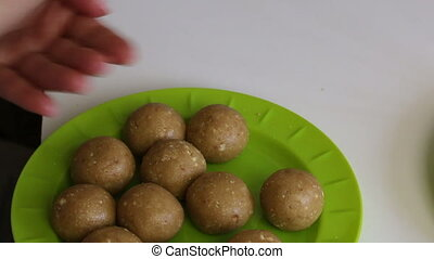 Woman shapes the cake pop cake blanks. Next to it in a cup with white chocolate is a popcake stick.