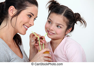 Woman sharing a glass of juice with her little sister