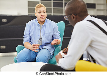 Portrait of masculine woman sharing mental health issues with African-American psychologist in therapy session or support group, copy space