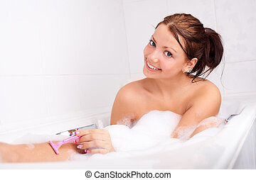 woman shaving legs - beautiful young brunette woman taking a...