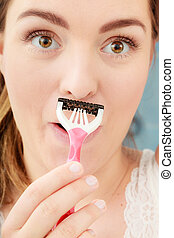 Woman shaving mustache with razor shaver. Hygiene.