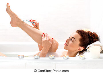 Woman shaving - Young and positive woman shaving her legs in...