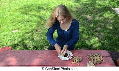 woman shell beans dish