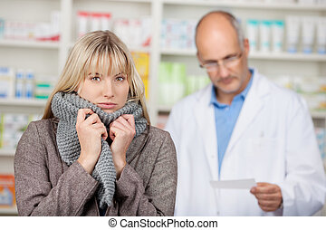 Woman Shivering With Male Pharmacists Reading Prescription