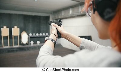 Woman shooting with a gun in shooting gallery, slow-motion,...