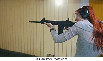 Woman shooting with a Mashin gun in shooting gallery, close...