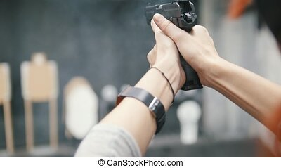 Woman shooting with a pistol gun in shooting gallery, close...