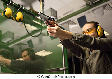 Woman shoots a gun at a shooting range.