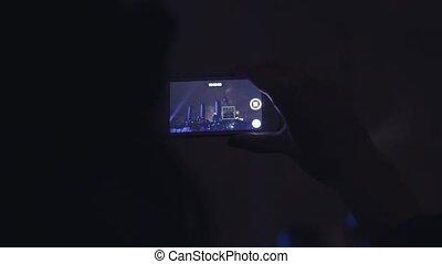 Woman shoots fireworks on a mobile phone - SAINT-PETERSBURG,...