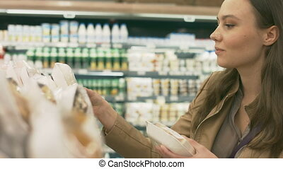 Woman shopper in the sweets section at the supermarket
