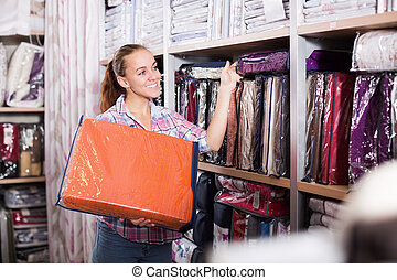 Woman shopper looking for beautiful bed linen in textile ...