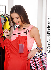 Woman shopping. Beautiful young woman holding red dress in retail store