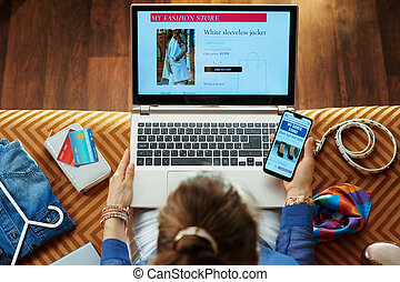 woman shopping clothes in online store on laptop and smartphone