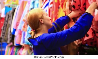 Woman shopping clothes. Shopper looking at clothing indoors in store. Beautiful blonde caucasian female model.