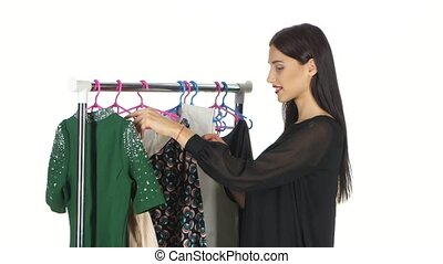 Woman shopping clothes. Shopper looking at clothing indoors in store. White