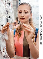 Woman shopping eyeglasses choosing between the models