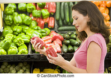 Woman shopping for bell peppers at a grocery store