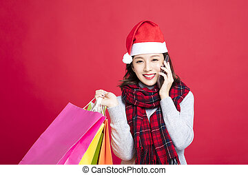 Woman shopping for christmas gifts and talking the phone