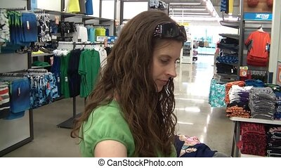 Woman Shopping for Clothes - Attractive young woman shopping...