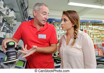 woman shopping for hammer drill in hardware store
