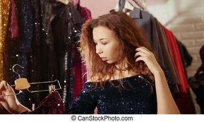 Woman shopping for new dress in clothing store