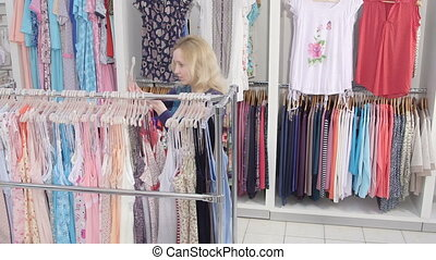 woman shopping for pregnancy clothes in baby and maternity shop