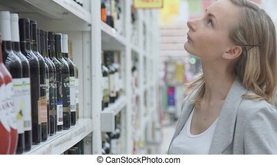 Woman shopping for wine or other alcohol in a bottle store standing in front of shelves full of bottles with a serious expression as she tries to make up her mind.