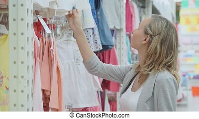 Woman shopping in a clothing store for children. children's clothes on hangers