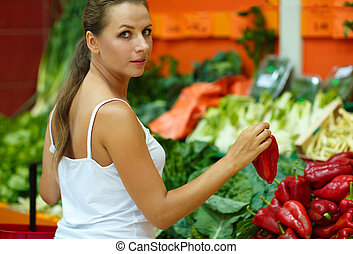 Woman shopping in a supermarket in the department of fruit and vegetables