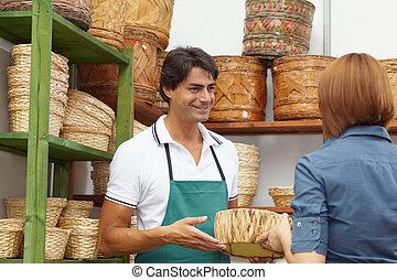 woman shopping in flower shop - rear view of woman talking...