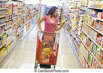 Woman shopping in supermarket aisle - Woman pushing trolley ...