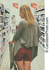 Woman shopping in the supermarket. Rear view.