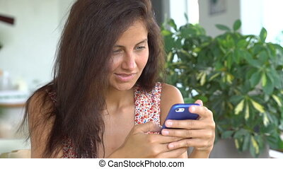 Woman shopping on smartphone in cafe.