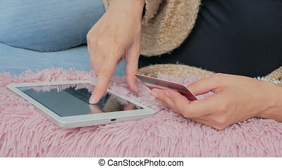 Woman shopping online at digital tablet with credit card