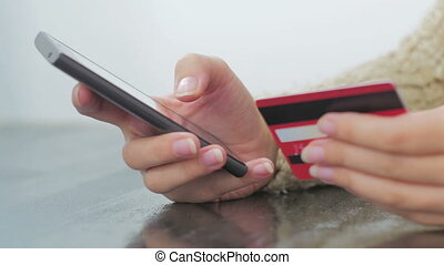 Woman shopping online at smartphone with credit card