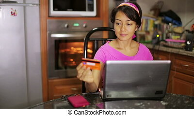 Woman shopping online in kitchen