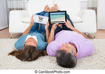 Woman Shopping Online While Man Watching Video