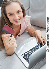 Woman shopping online with her laptop smiling at camera