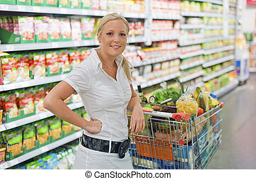 woman shopping with cart in the supermarket