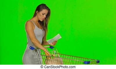 Woman shopping with trolley at supermarket and checking a paper list. Green screen