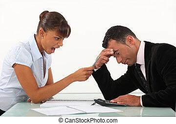 Woman shouting at a man across a desk