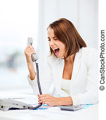 Woman shouting into phone in office