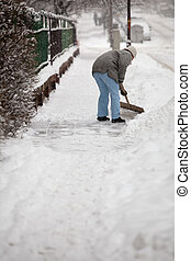 Woman shoveling snow from the sidewalk in front of his house after a heavy snowfall in a city (focus on the fence in the foreground)