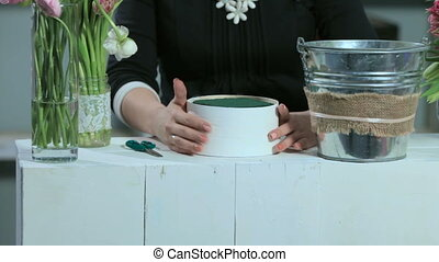 Woman show a flower arrangement in the round form white box...