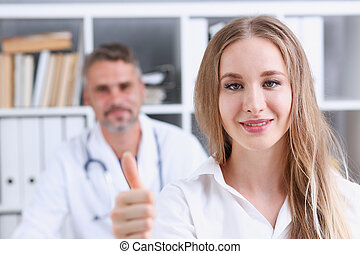 Woman show ok or confirm with thumb up at doctor office...