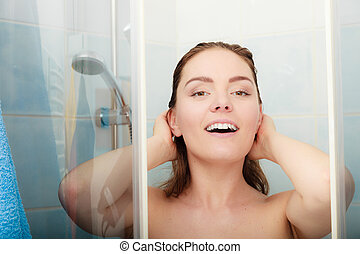 Woman showering in shower cabin cubicle.