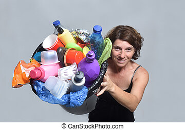 woman showing a bin full of plastic garbage for recycling