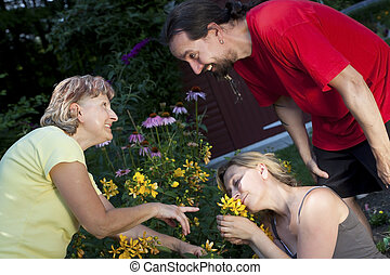 Woman showing a couple flowers in the garden